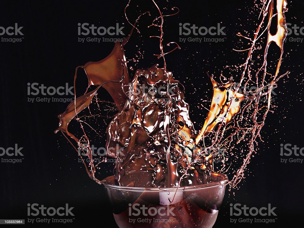 Close up of chocolate syrup splashing from glass royalty-free stock photo