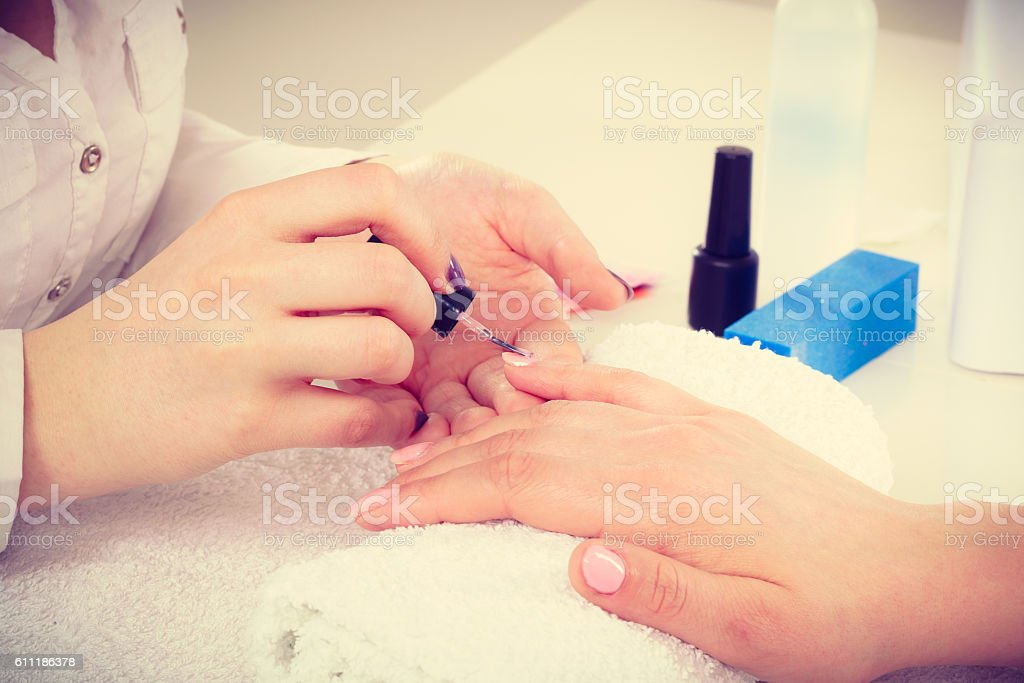 Close up of client and manicurist hands. stock photo