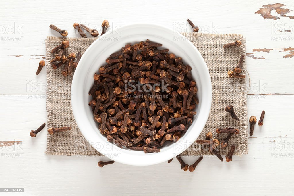 Close up of cloves in cup on white wooden table stock photo