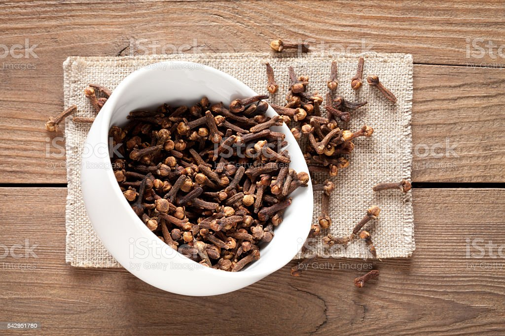 Close up of cloves in cup on wooden table stock photo