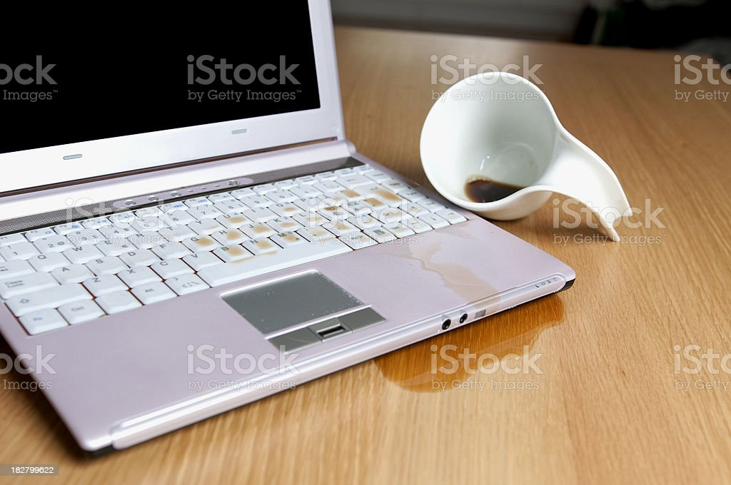 Close up of coffee cup spilled al over computer royalty-free stock photo