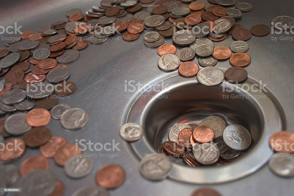Close up of coins in a sink and going down the drain stock photo
