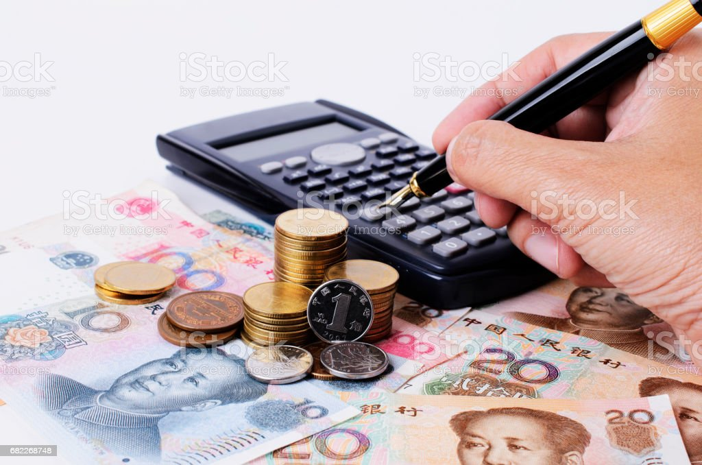 Close up of coins stack and calculator with fountain pen stock photo
