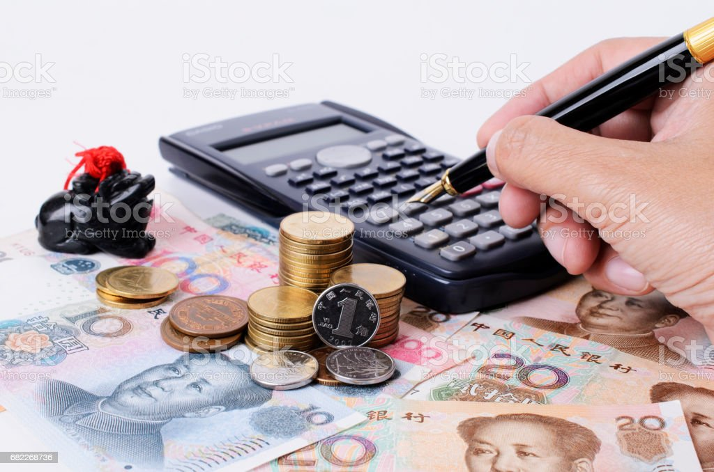 Close up of coins stack and pressing calculator with fountain pen stock photo
