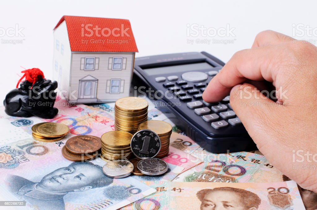 Close up of coins stack with pressing calculator  for mortgage loans concept stock photo