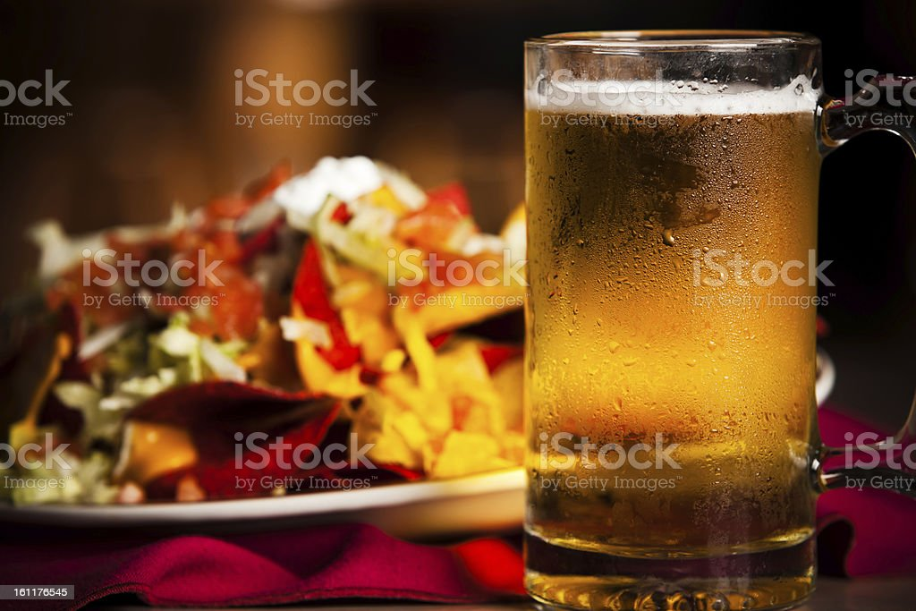 Close up of cold beer and blurred plate of nachos stock photo