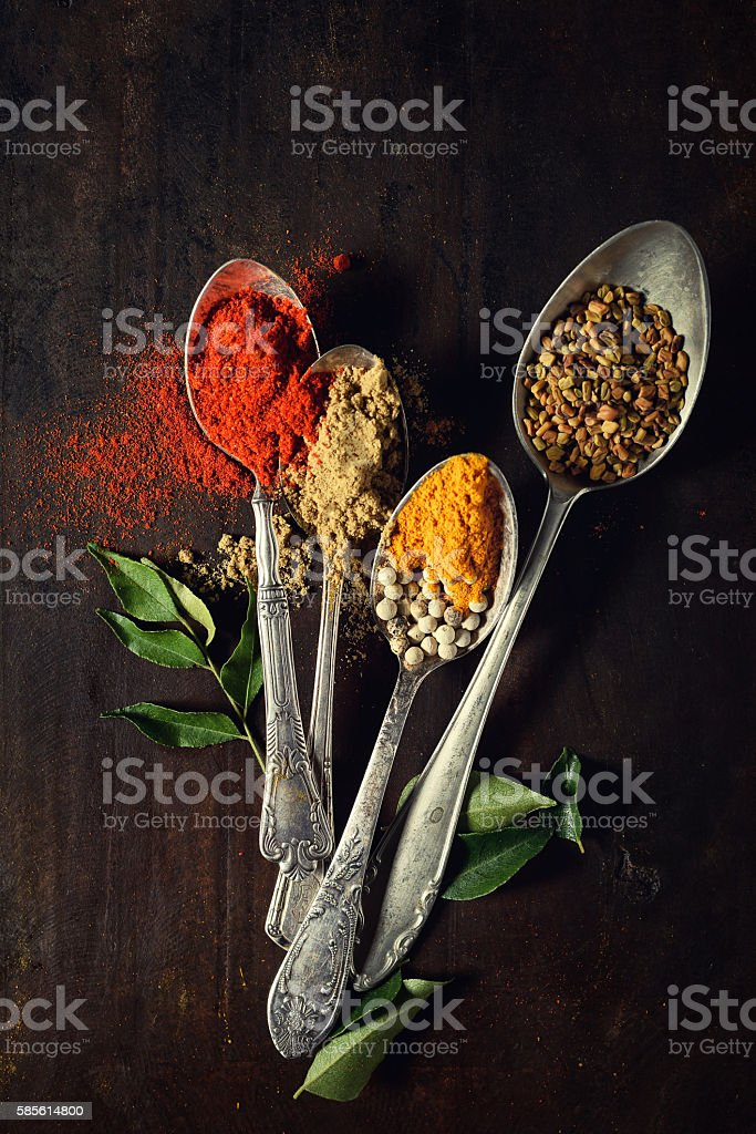 Close up of colorful spices in spoons. stock photo