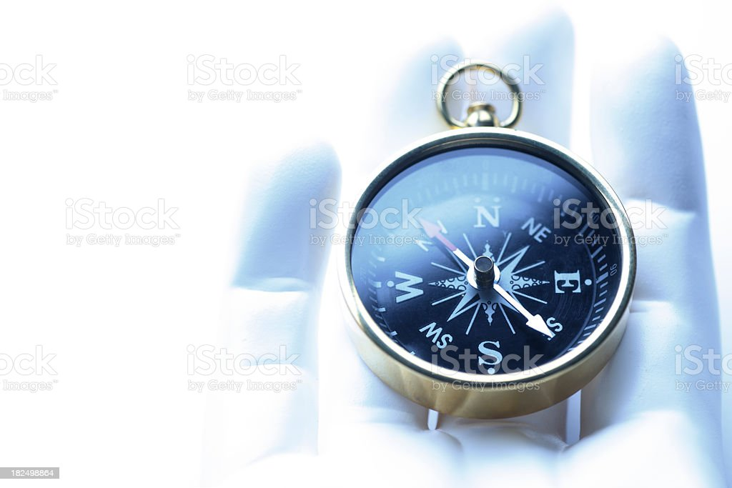 Close Up Of Compass Lying In Synthetic Hand stock photo