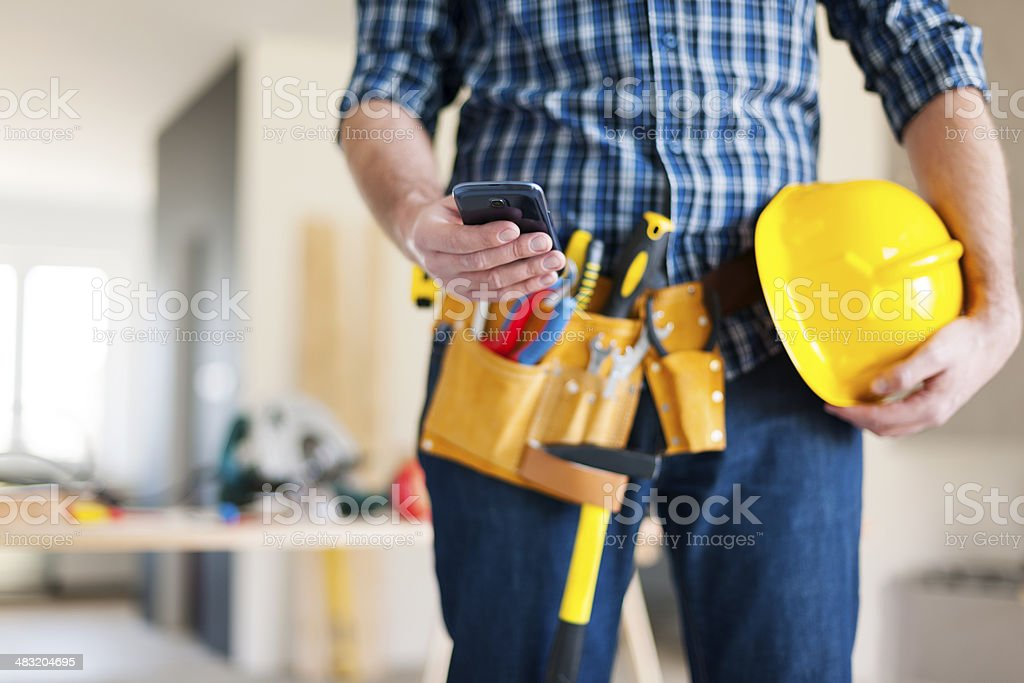 Close up of construction worker with mobile phone stock photo