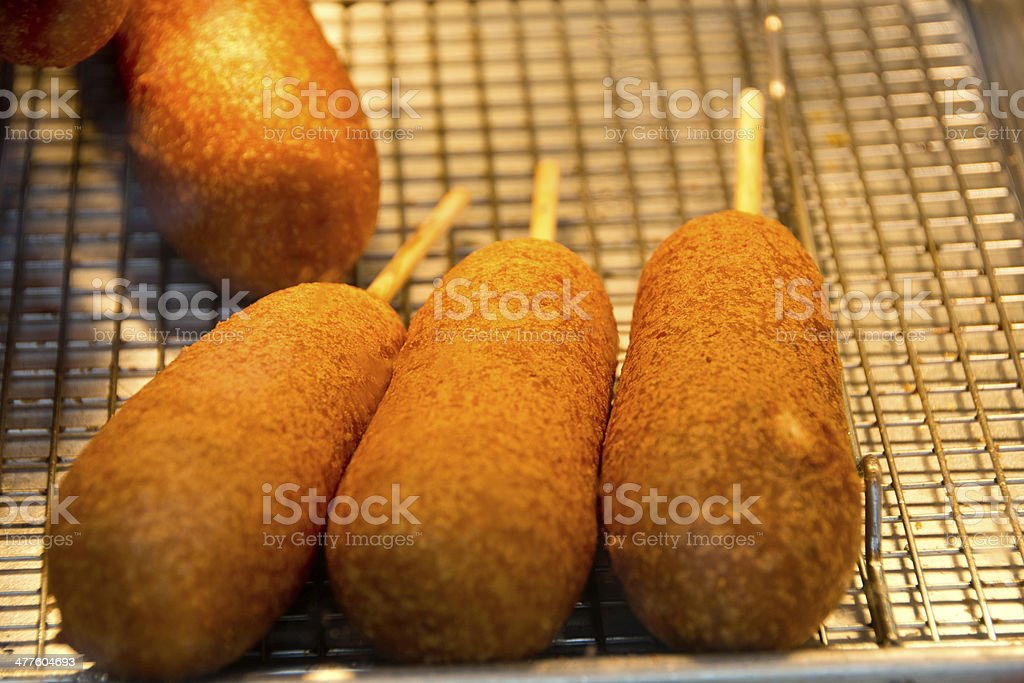 Close up of corn dogs under a heat lamp stock photo