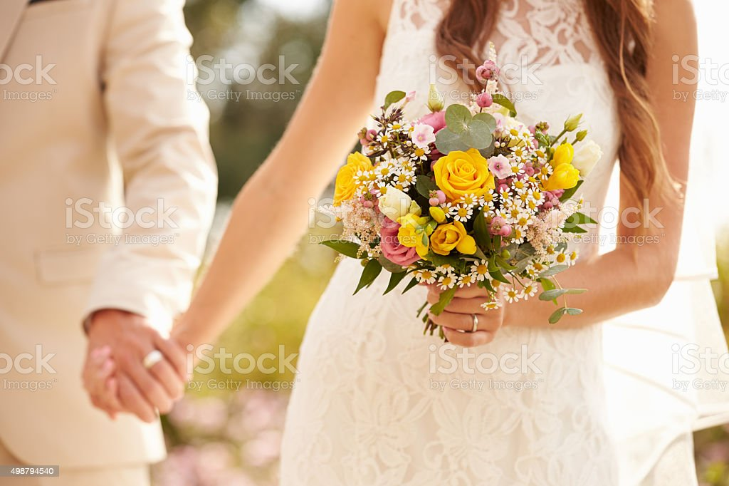 Close Up Of Couple At Wedding Holding Hands stock photo