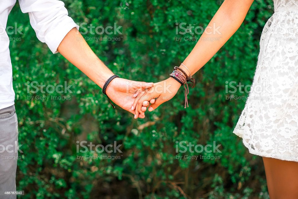 Close up of couple holding hands stock photo