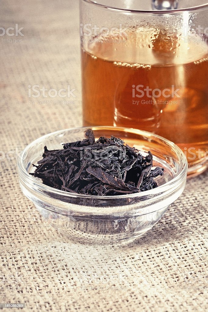 Close up of cup of tea with dried tea leaves royalty-free stock photo