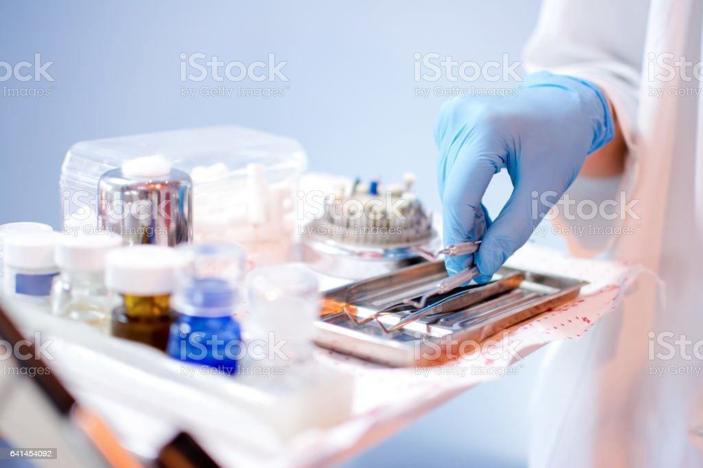 Close up of dentist's hands picking up dental equipment. stock photo