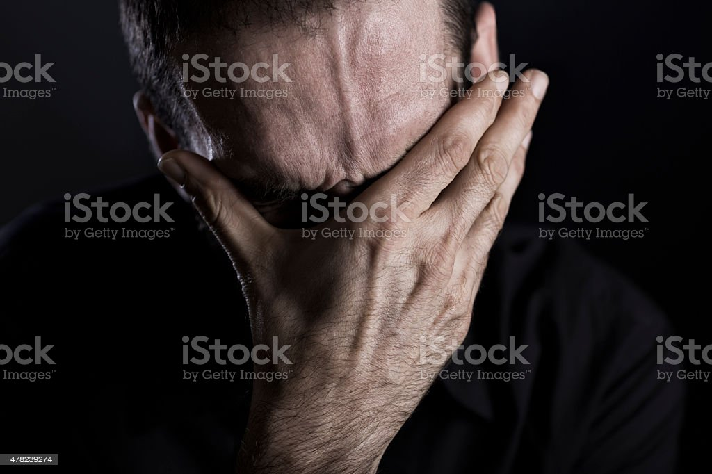 Close up of depressed and despaired man. stock photo