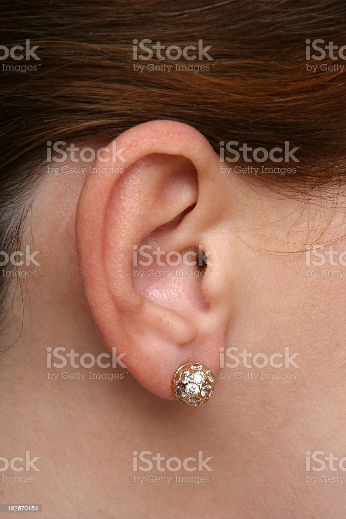 Close up of diamond earring in woman's ear stock photo