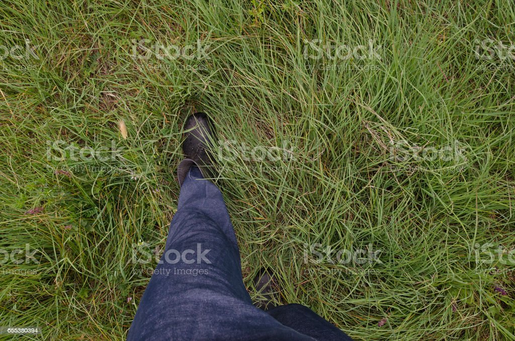 Close up of dirty and wet boots on the green grass stock photo