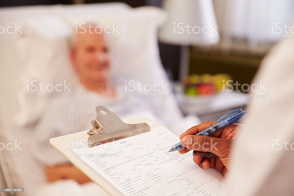 Close Up Of Doctor Writing On Senior Male Patient's Chart stock photo