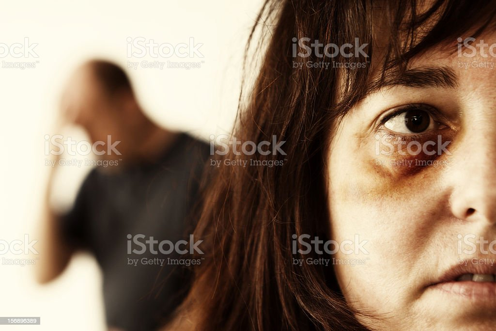 Close up of domestic abuse victim, man in background stock photo