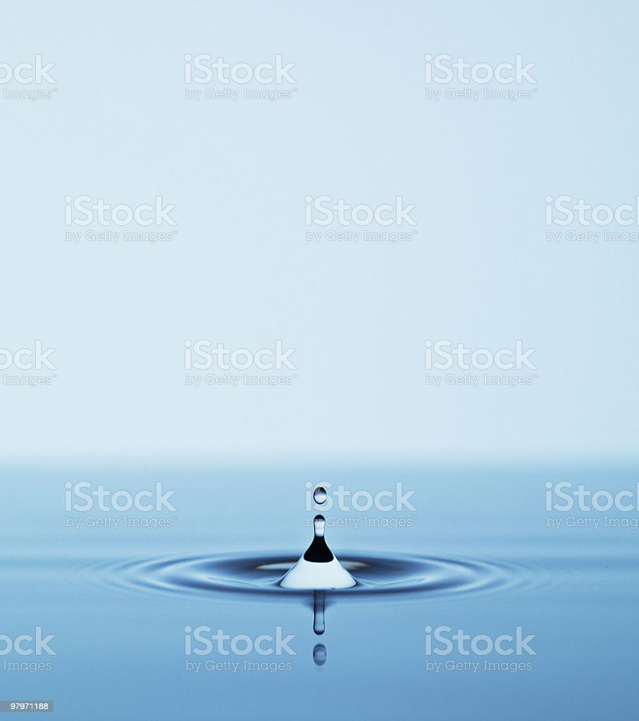 Close up of droplet falling in pool of water stock photo