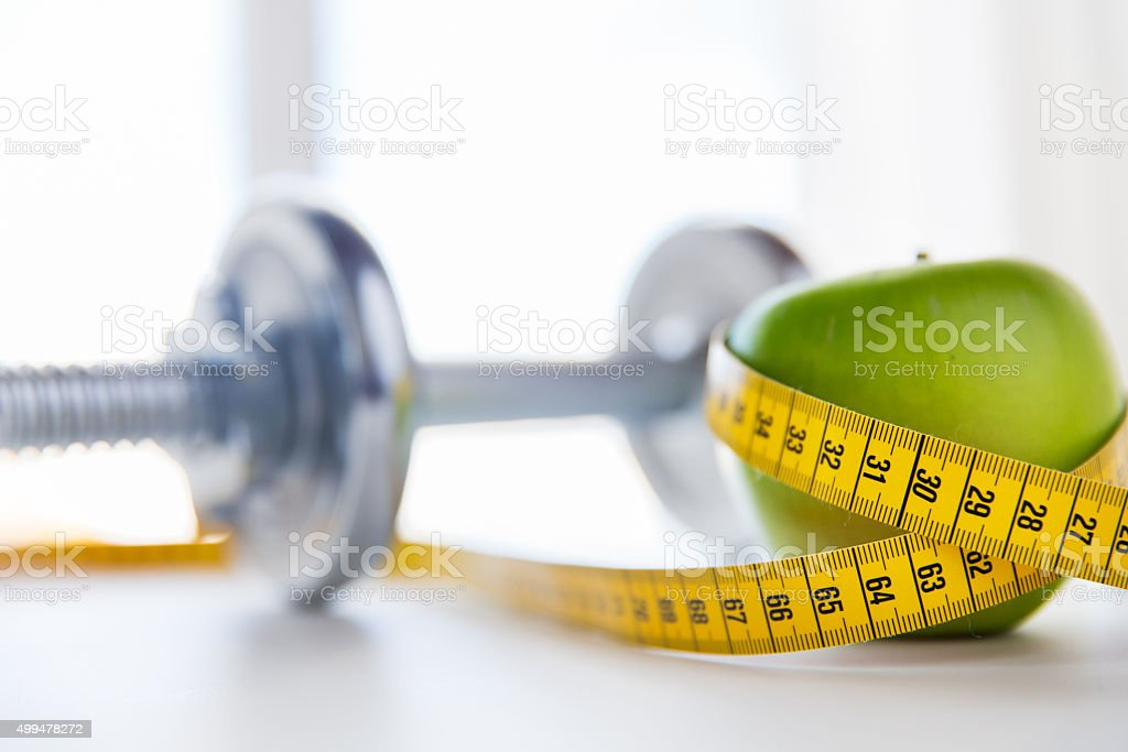 close up of dumbbell and apple with measuring tape stock photo