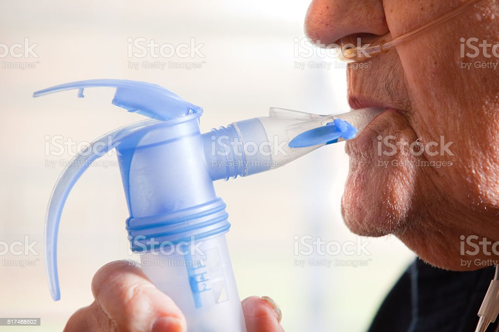 Close Up Of Elderly Man Using Nebulizer stock photo