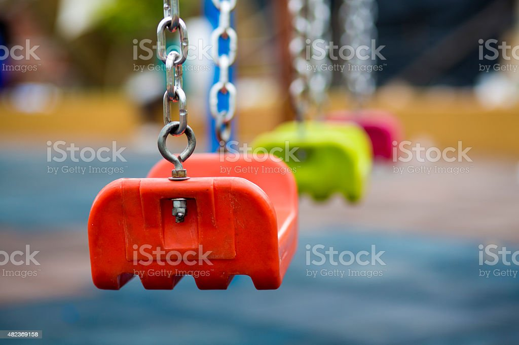 Close up of empty swing in a playground stock photo