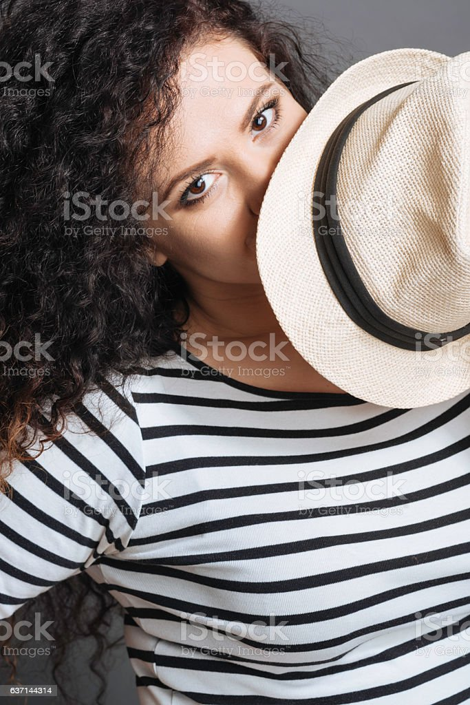 Close up of enigmatical female covering her lips stock photo