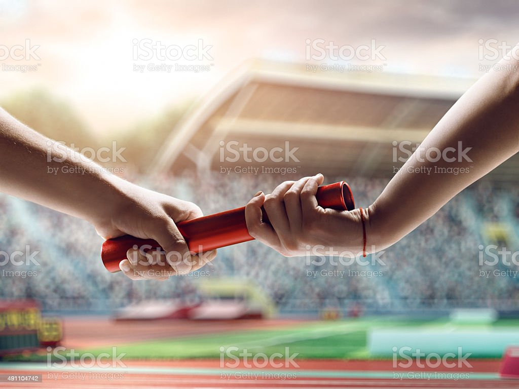 Close up of exchanging relay baton on a race stock photo