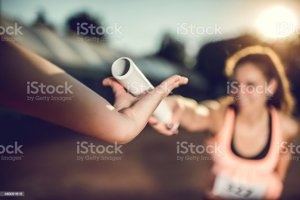 Close up of exchanging relay baton on a sports race. stock photo