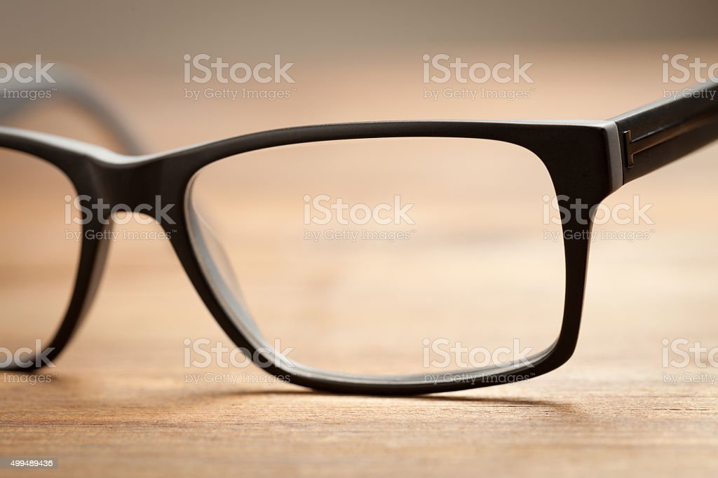 Close up of eye glasses on wooden table stock photo
