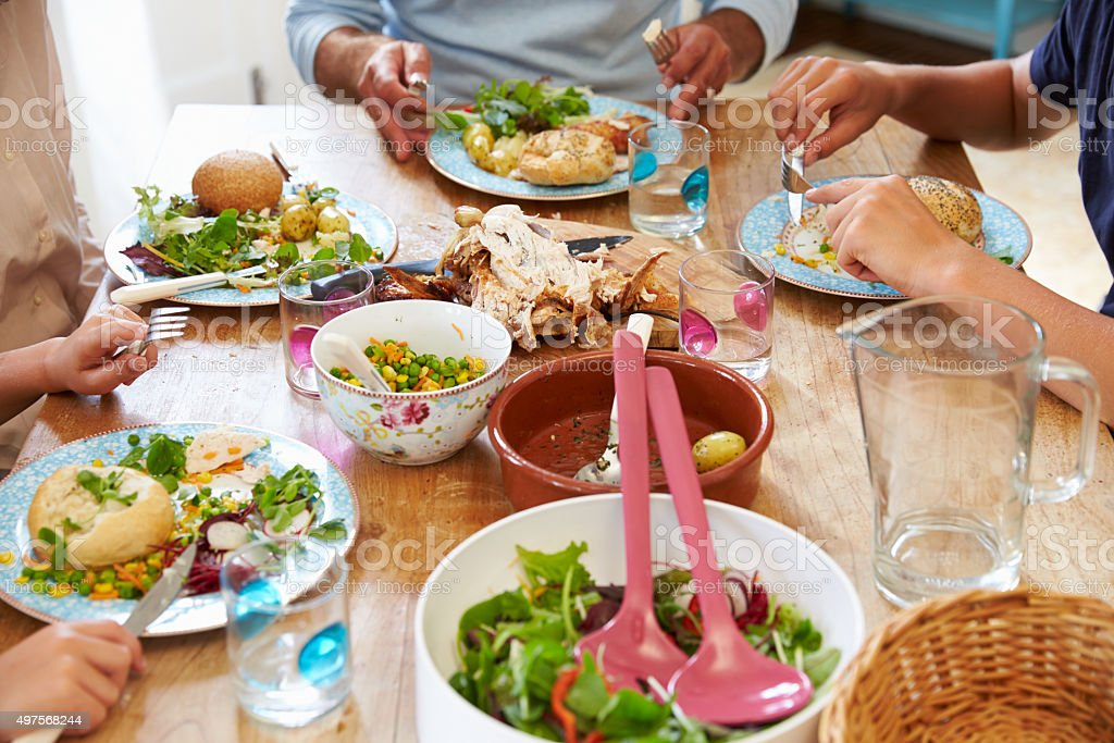 Close Up Of Family Sitting At Table Enjoying Meal stock photo