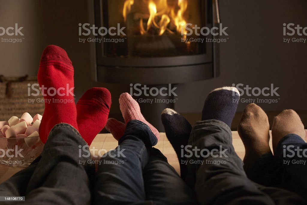 Close Up Of Familys Feet Relaxing By Cosy Log Fire stock photo