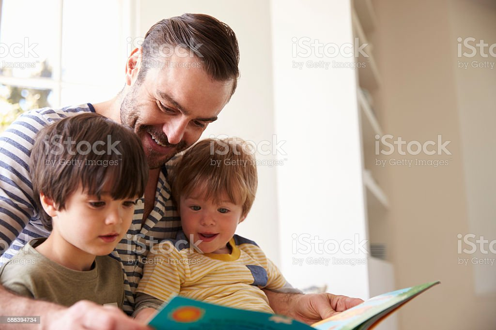 Close Up Of Father And Sons Reading Story At Home stock photo