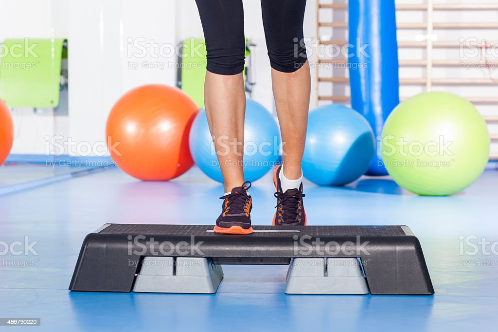 Close up of feet in step equipment at gym. stock photo