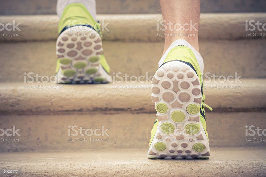 Close up of feet with sneakers climbing up the stairs stock photo