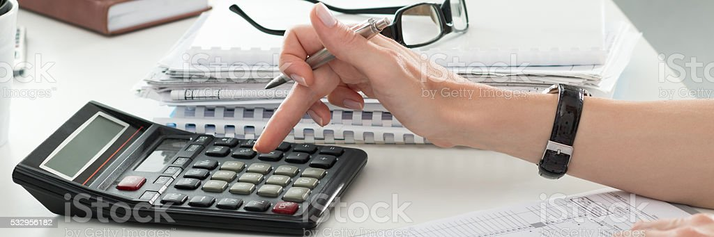 Close up of female accountant or banker making calculations stock photo