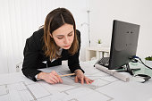 Close Up Of Female Architect With Blueprint On Desk