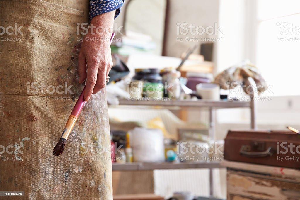 Close Up Of Female Artist Holding Brush In Studio stock photo
