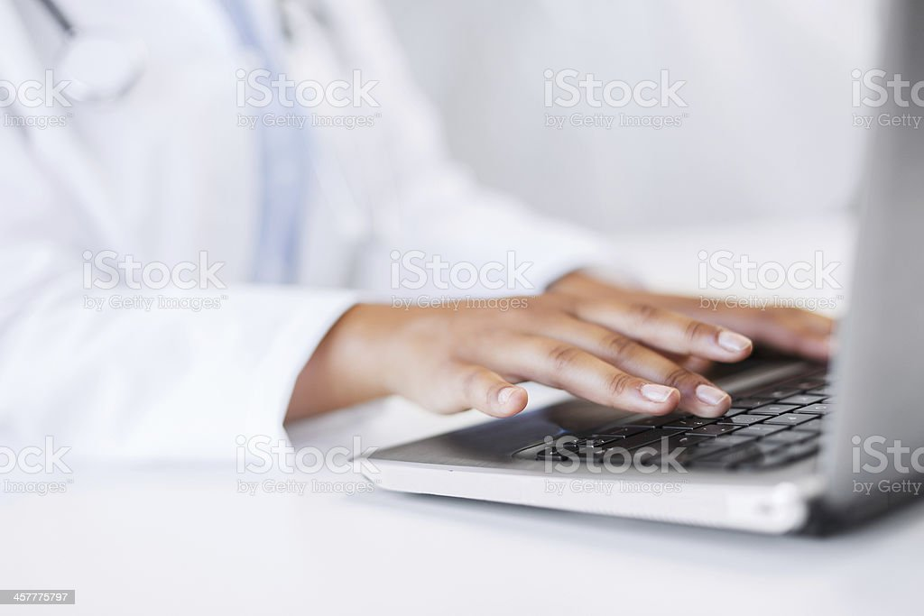 close up of female doctor hands typing on laptop computer stock photo