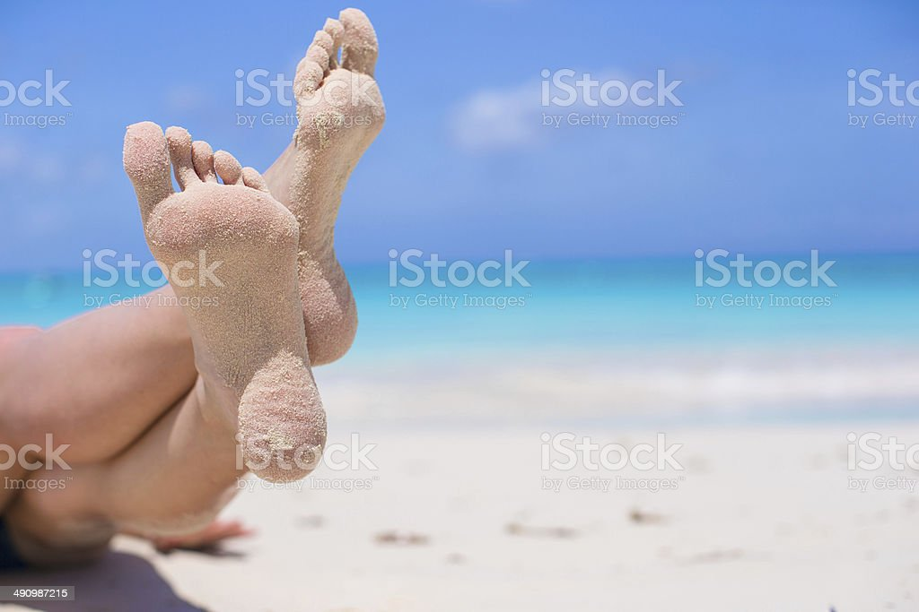 Close up of female feet on white sandy beach royalty-free stock photo