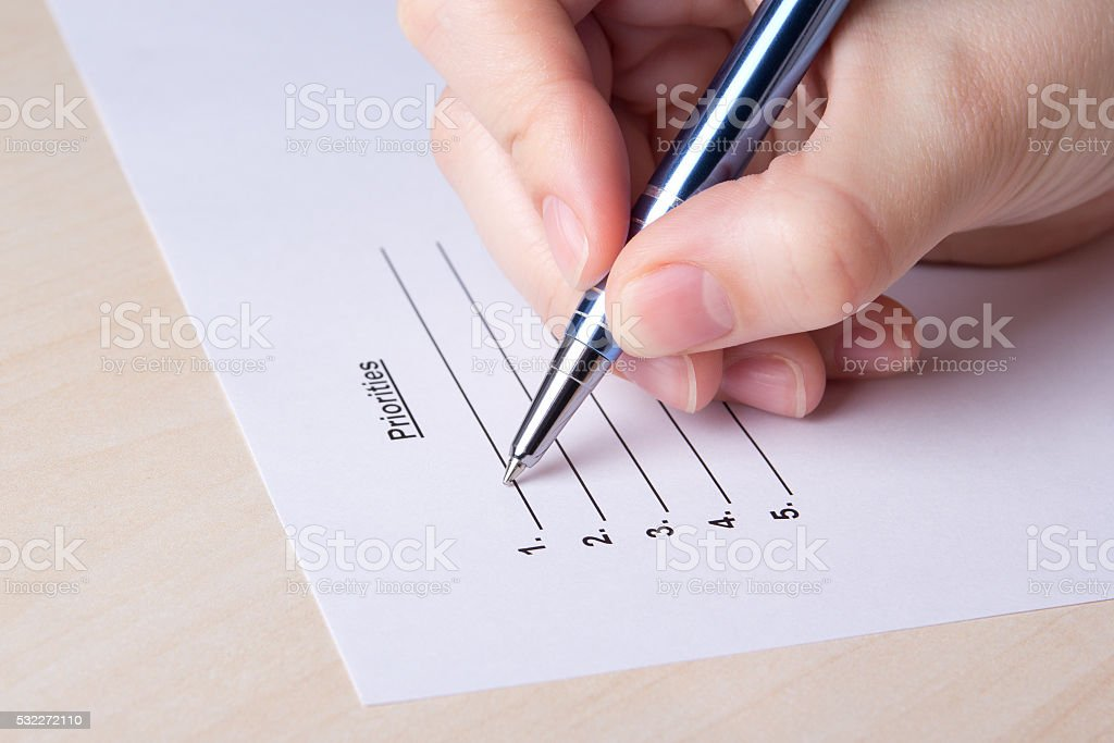close up of female hand filling priorities list with pen stock photo