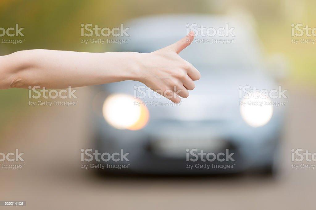 Close up of female hand hitchhiking stock photo
