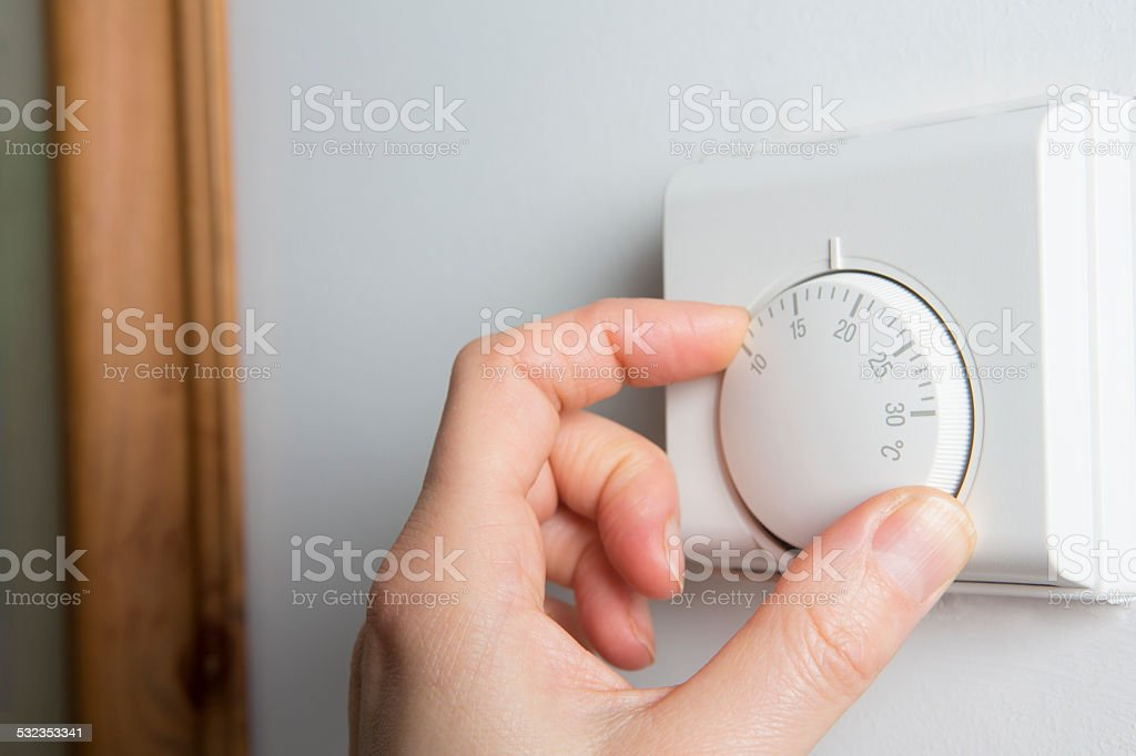 Close Up Of Female Hand On Central Heating Thermostat stock photo