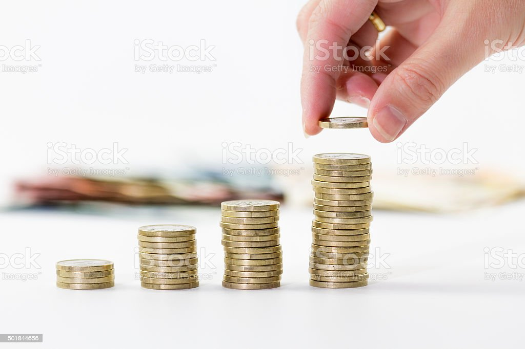 Close up of female hand stacking euro coins stock photo