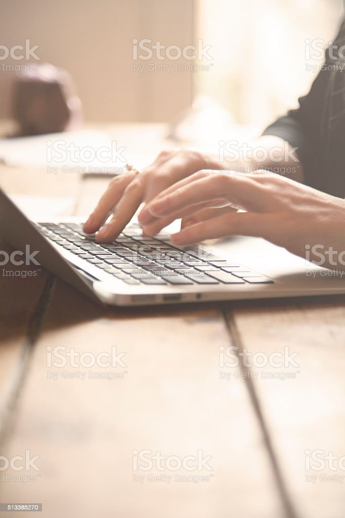 Close up of female hands working on a laptop stock photo