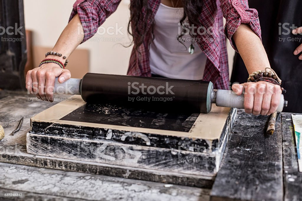 Close up of female lithograph worker using rolling pin stock photo