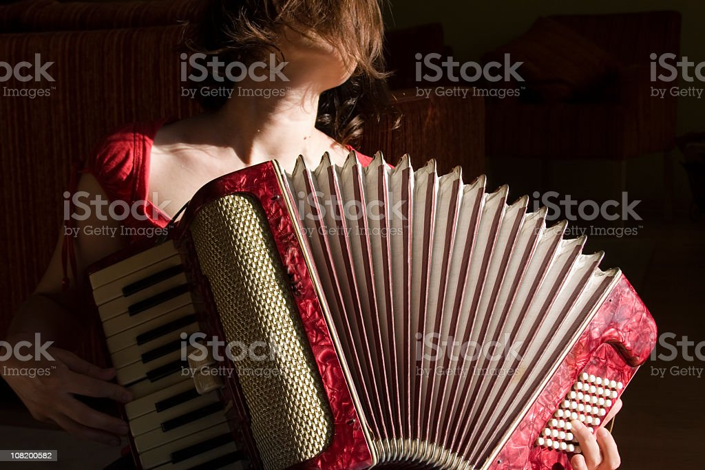 Close up of female playing red vintage accordion stock photo
