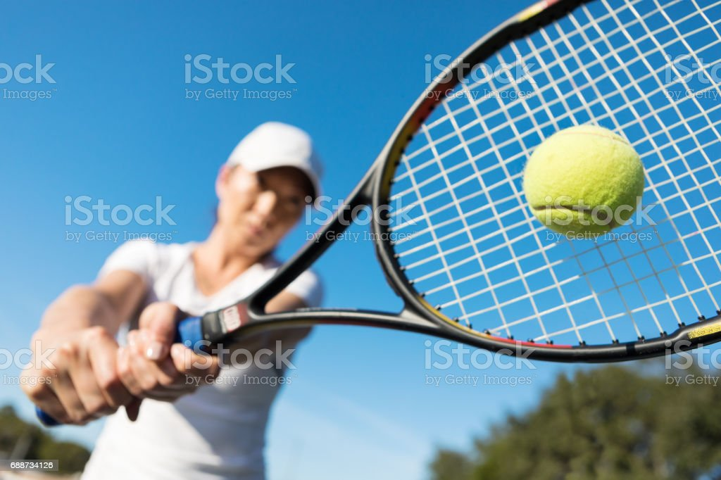 Close up of female tennis player hitting the ball stock photo