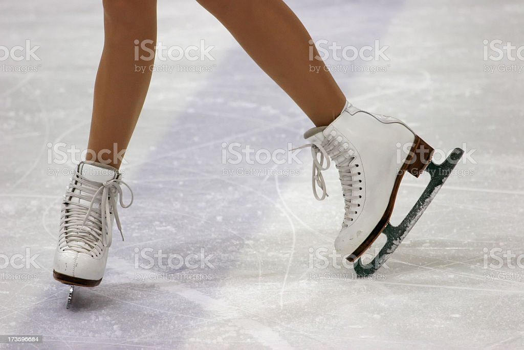 Close up of figure skaters feet in skates on ice stock photo